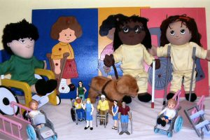 Inclusive kit containing glasses, seeing eye dog, wheelchair, dolls, puzzles and more.