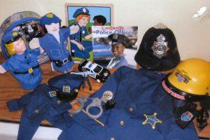 Includes police helmet, uniform, puppets, book, puzzle, doll's uniform.